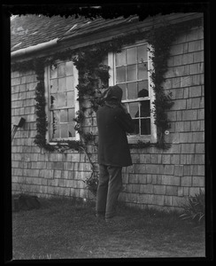 Thumbnail of Reuben Austin Snow, the cross-dressing hermit of Cape Cod, looking in the cottage window