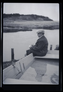 Thumbnail of Unidentified man seated on a the edge of rowboat, looking over a pond