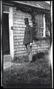 Thumbnail of Reuben Austin Snow, the cross-dressing hermit of Cape Cod, wearing a top hat          outside the cottage
