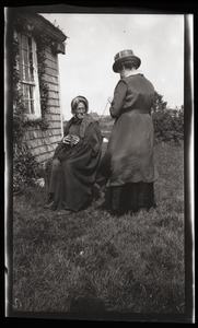 Thumbnail of Reuben Austin Snow, the cross-dressing hermit of Cape Cod Seated outside cottage, knitting, with unidentified woman holding yarn