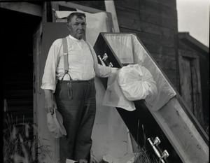 Thumbnail of George F. Stone, the man who made his own coffin Posed next to coffin, laid out in front of a shed