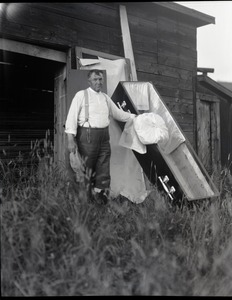 Thumbnail of George F. Stone, the man who made his own coffin Posed next to coffin, displaying a pillow