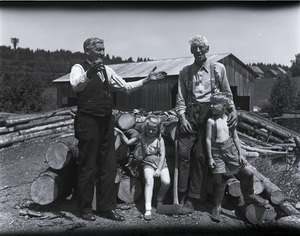 Thumbnail of Abe Washburn Standing by a woodpile with an unidentified man and children