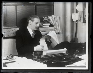 Thumbnail of Walter Winchell, seated at his typewriter, smoking a cigarette and reading copy of his column