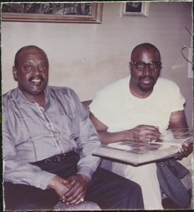 Thumbnail of Ben Webster seated with Yusef Lateef, looking at photographs