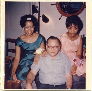 Thumbnail of Bernie Moss seated on a sofa between two women