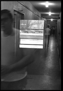 Thumbnail of Double exposure: window superimposed on people walking in a hallway