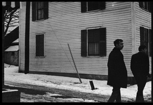 Thumbnail of Two men walking past a house in the snow