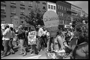 Thumbnail of Crowd at the Northampton Pride Parade: crowd with signs on Main Street,             including opponent carrying sign 'Homosexuals are a disgrace to the human race'