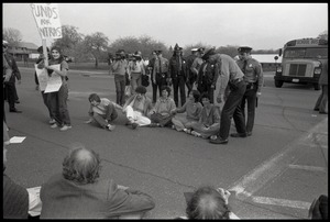 Thumbnail of Protests against U.S. intervention in Nicaragua at Westover Air Force             base: police closing in on five women protesters seated on the ground and holding hands