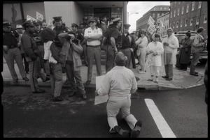 Thumbnail of Pro-life protester on his knees, facing a line of police in front of the Providence Planned Parenthood clinic