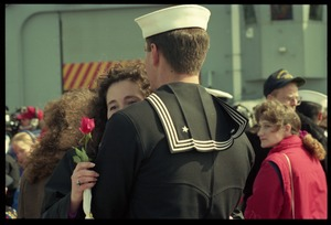 Thumbnail of Woman with a rose hugging a sailor from the USS Roberts returning from Persian             Gulf War duty