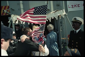 Thumbnail of Sailor hugging a woman behind flags upon the USS Roberts returning from Persian Gulf War duty
