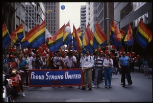 Thumbnail of Group marching in the San Francisco Pride Parade with pride flags and banner             reading 'Proud / strong / united 1987'