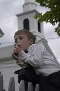 Thumbnail of Church supper at the First Congregational Church, Whately: boy blowing on the       seed head of a dandelion in front of the church