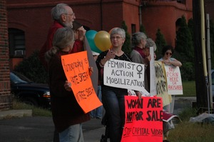 Thumbnail of Protest against a proposed pornographic video store in Northampton: protesters with signs reading 'Feminist Action Mobilization' and 'Women are not             for sale / Stop Capital Video'