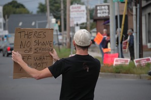 Thumbnail of Protest against a pornographic video store in Northampton: counter-protester             holding sign reading 'Theres no shame of showing off what you got!'