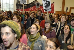 Thumbnail of UMass student strike: audience in the Student Union ballroom chanting and             holding signs supporting a general student strike