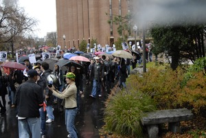 Thumbnail of UMass student strike: strike organizer with a bullhorn, leading the march past             the Du Bois Library