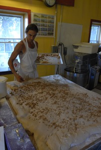 Thumbnail of Hungry Ghost Bread: owner and baker Jonathan C. Stevens spreading filling dough for cinnamon rolls
