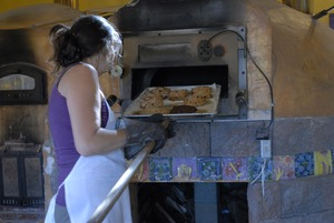Thumbnail of Hungry Ghost Bread: owner and baker Cheryl Maffei removing cookies from the oven