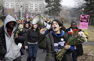 Thumbnail of Justice for Jason rally at UMass Amherst: UMass student Talleen Navarian shouts             chants into a bullhorn as she an other students and staff rally through campus in             support of Jason Vassell