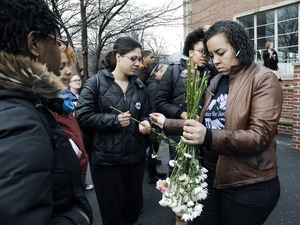 Thumbnail of Justice for Jason rally at UMass Amherst: Tracy Kelley, right, of the Committee             for Justice for Jason Vassell, hands out flowers to students and staff marching in             support of Vassell