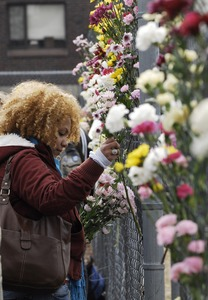 Thumbnail of Justice for Jason rally at UMass Amherst: UMass graduate student Iris Jacob,             places a flower on a fence near the dormitory of  Jason Vassell
