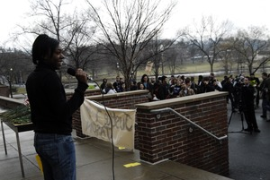 Thumbnail of Justice for Jason rally at UMass Amherst: speaker on the south deck of the             Student Union building at the rally in support of Jason Vassell