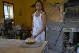 Thumbnail of Hungry Ghost Bread: owner and baker Jonathan C. Stevens removing loaves of bread         from the oven