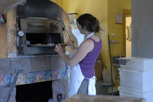 Thumbnail of Hungry Ghost Bread: owner and baker Cheryl Maffei putting cookies into the oven