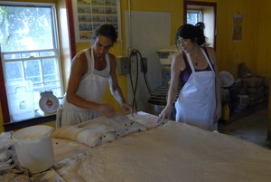 Thumbnail of Hungry Ghost Bread: owners and bakers Jonathan C. Stevens and Cheryl Maffei working dough for cinnamon rolls