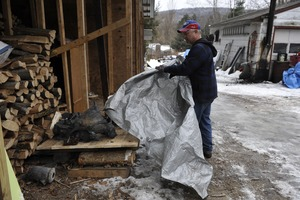 Thumbnail of Aftermath of the Congregational Church fire in West Cummington, Mass.:             man pulling a tarp away from the charred remains of the church bell