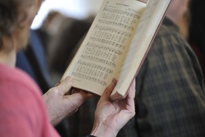 Thumbnail of Aftermath of the Congregational Church fire in West Cummington, Mass.:             close-up of parishioner singing from a hymnal