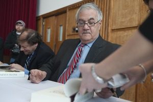 Thumbnail of Author Stuart Weisman and Congressman Barney Frank (l. to r.) seated at a table in the Student Union Ballroom stage,             UMass Amherst, signing copies of his biography