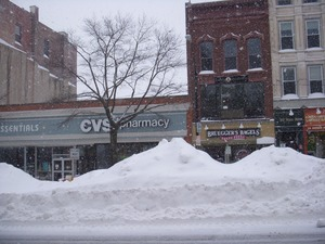Thumbnail of Plowed snow piled high in the middle of Main Street, Northampton, Mass., near             intersection with Gothic St. CVS Pharmacy and Bruegger's Bagels in background