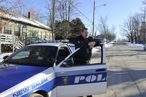 Thumbnail of New Salem town police officer standing by his patrol car in front of the Stowell             building