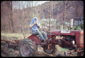 Thumbnail of Tony Mathews driving a tractor, Montague Farm commune