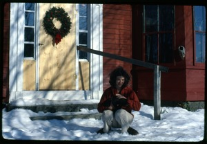 Thumbnail of Nina Keller seated in the snow with cat, in front of the door, Montague Farm Commune