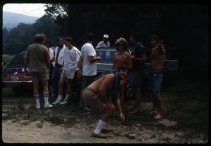 Thumbnail of Twentieth reunion gathering, Montague Farm Commune Communards gathered around parked cars, including (l. to r.) Chuck Light (far             left back to camera), Tony Mathews (bending down), Nina Keller, Dan Keller, Harvey Wasserman