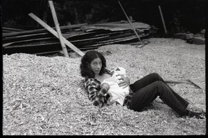 Thumbnail of Nina Keller feeding her baby on a pile of woodchips, Montague Farm Commune