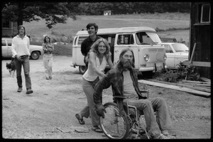 Thumbnail of Janice Frey pushing Peter Natti in a wheelchair, Tony Mathews behind, Montague Farm Commune