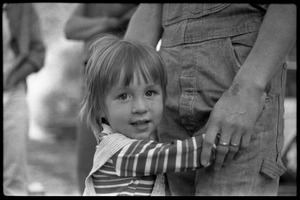 Thumbnail of Child hugging the legs of her mother, Montague Farm Commune