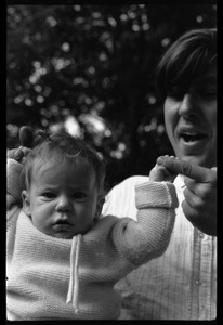 Thumbnail of Tony Mathews holding an infant, Montague Farm commune