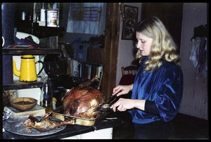 Thumbnail of Janice Frey carving a turkey at Christmas dinner, Montague Farm commune