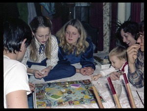 Thumbnail of Playing a board game at Christmas time, Montague Farm commune Group includes Sequoya and Janice Frey (second and third from left), Harvey             Wasserman (far right)