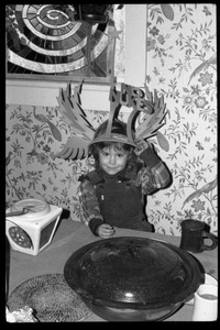 Thumbnail of Child seated at a table, wearing a winged No Nukes headdress, Montague Farm commune
