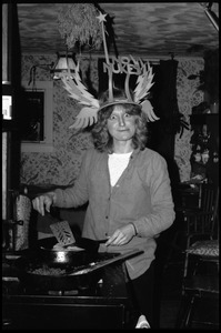 Thumbnail of Janice Frey at the stove, making a silly face, wearing a winged No Nukes headdress, Montague Farm commune