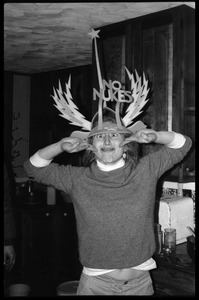 Thumbnail of Unidentified person making a silly face, wearing a winged No Nukes headdress, Montague Farm commune