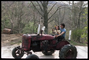 Thumbnail of Tony Mathews with young child, driving a tractor, Montague Farm commune